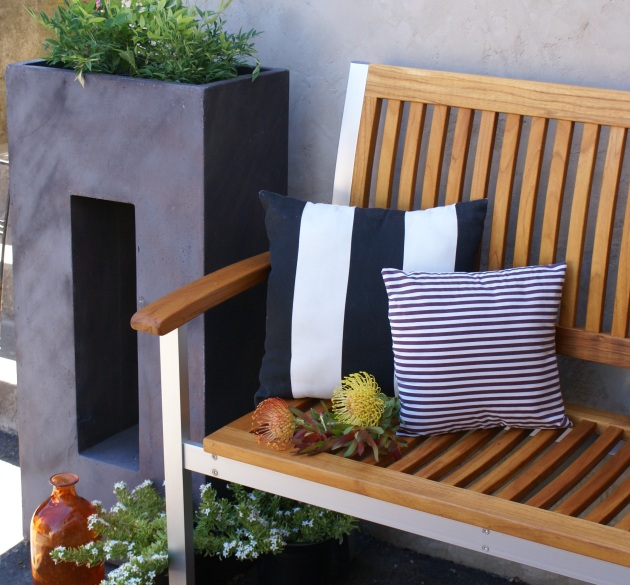 modern planters with striped outdoor pillows and contemporary teak bench
